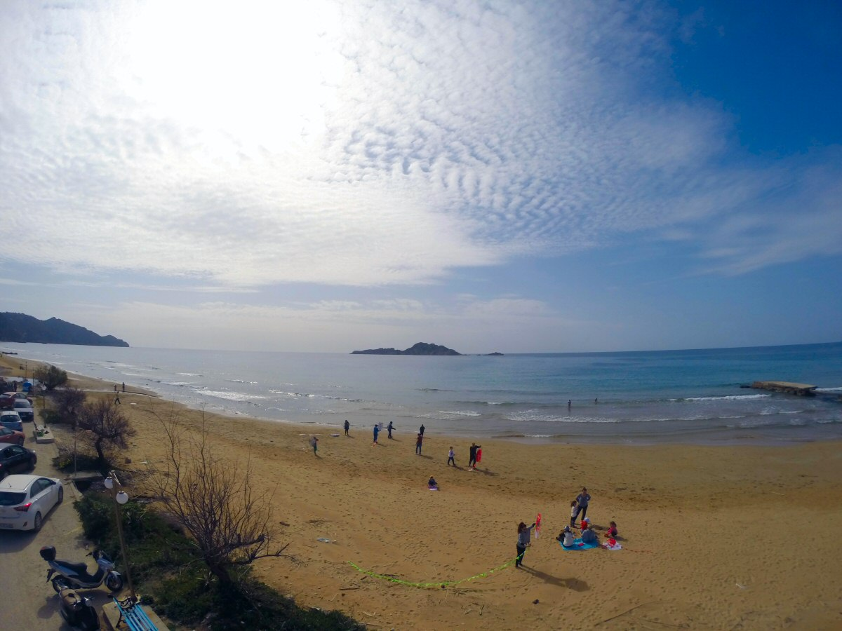 Aerial View of Arillas beach showing families flying kites